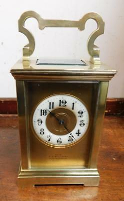 large brass cased mask dial striking carriage clock. fillery eastbourne