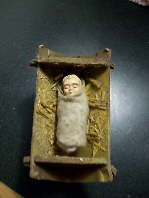 Tiny baby Jesus wrapped in swaddling clothes in manger nativity creche figure