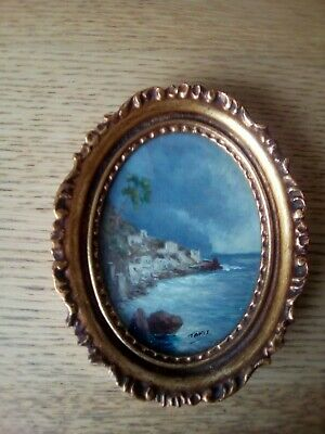 Miniature mid 20thc oval oil painting of a coastal scene with white buildings.