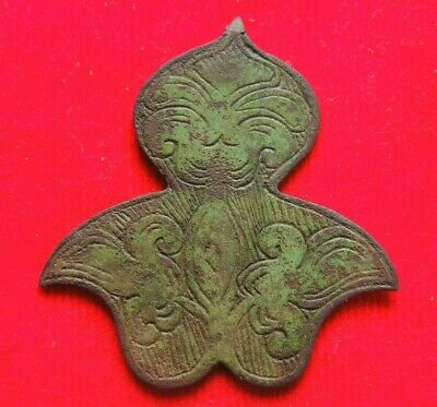 Ancient bronze artifact with a silhouette of a human face