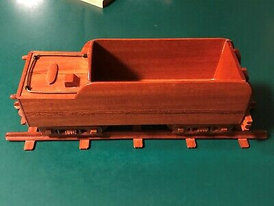 hand carved rail road car made of wood with tracks to sit the train on