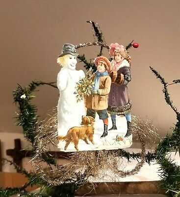 Children placing Holly into hand of Smiling Snowman. Tinsel & Paper Christmas