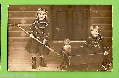#F.   Postcard - Young Girls  With Cart & Doll