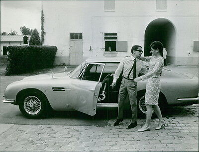 Vintage photo of A man and a woman standing outside the car. -