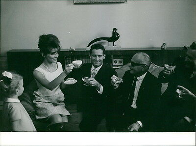 Vintage photo of Irina Demich toasting drinks with other people.  -