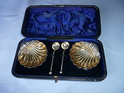 A pair of Victorian shell shaped sterling silver salt bowls & pair of spoons