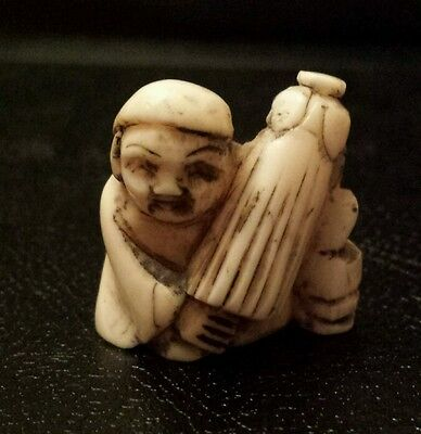 A 19th Century Japanese carved Netsuke of a figure with a parasol.