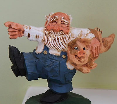 Jovial old man standing on1 leg holding pig under his arm Base mounted in resin