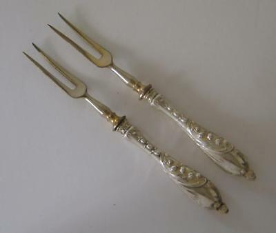 A Pair Of Ornately Embossed Antique Solid Silver Handled Pickle Forks