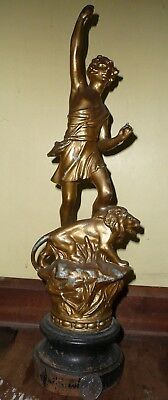antique figure,spelter body of a man stood behind a roaring Lion
