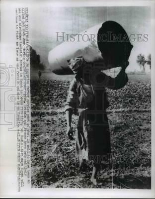 1956 Press Photo An Egyptian Farmer carries part of Allied jet shot down