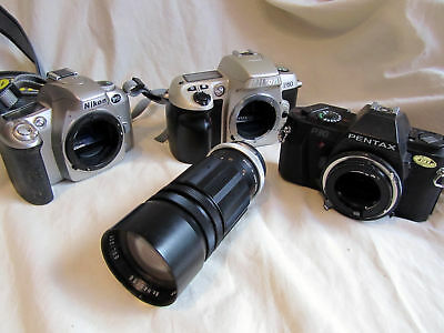 3 Old Camera Bodies And A Telephoto Lens