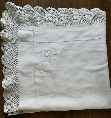 Vintage white tablecloth with lace edging and white embroidered flowers.