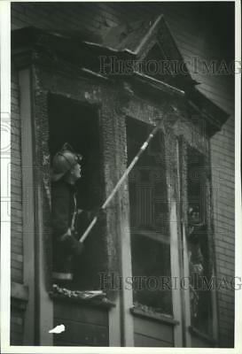 1993 Press Photo Firefighter Examines Fire Damage to Milwaukee Rooming House