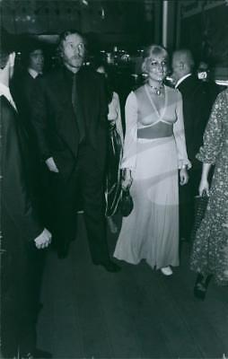 Richard St John Harris with a woman seen arriving at a party. - Vintage photo