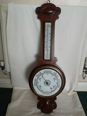 Antique large mahogany wheel barometer and thermometer with pottery dial.