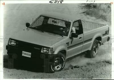 Press Photo Mazda B2200 Four by Four Pickup Truck Driving on Dirt Path