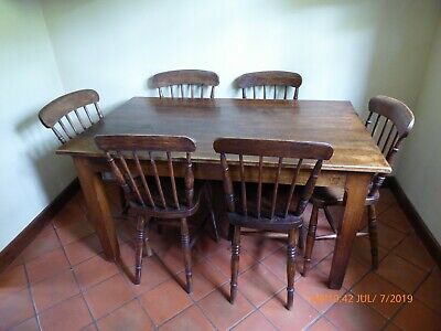Solid oak antique table together with six very old stick back chairs