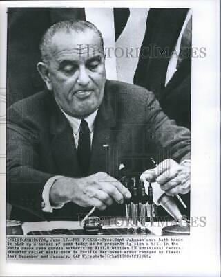 1965 Press Photo President Johnson Uses Both Hands to Pick Up a Series of Pens