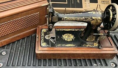 Antique, hand crank Singer sewing machine in original carved wooden box.