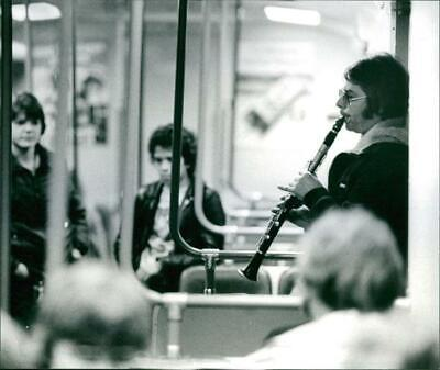 Woman plays clarinet on the subway - Vintage Photograph