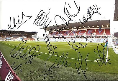 A 12 x 8 inch photo featuring Turf Moor, personally signed by 12 Burnley players
