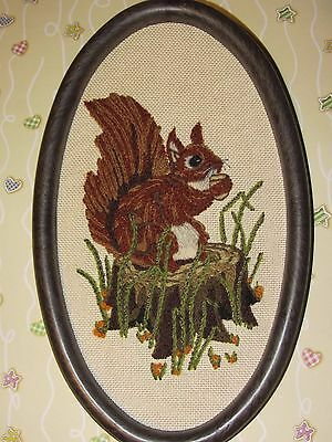 Embroidered in wool, red squirrel with acorn on tree trunk, picture