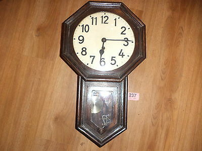 Antique wooden wall clock with pendulum