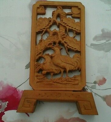 Oriental carved wooden decorated plaque with stand.