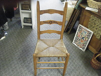 Antique ladder back chair with rush seat. and black flower stencil