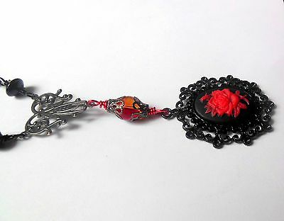 Black, red necklace with red rose cameo pendant and glass beads.