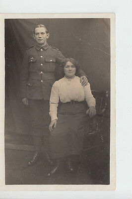 Portrait postcard showing soldier with his sweetheart. Service Award above pocke
