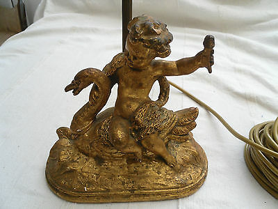 An old gold baroque style lamp base with a cherub riding a swan
