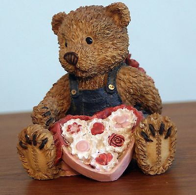 Male teddy bear holding a big candy heart with a flower bouquet behind his back