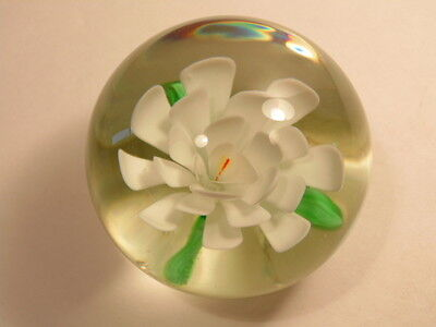 Older large clear glass paperweight with white flowers on green leaves