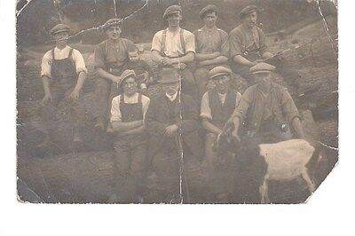 Agricultural workers / Foresters sitting on large tree trunk also goat & boy