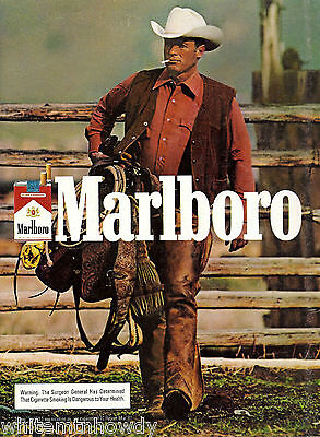 1982 MARLBORO MAN CIGARETTES AD~Cowboy in Chaps Carrying Saddle