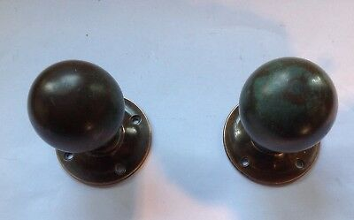 A vintage pair of tarnished copper door knobs