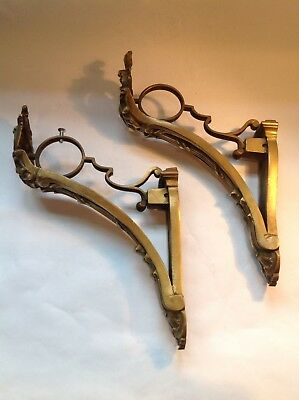 A pair of brass antique ornate curtain pole brackets