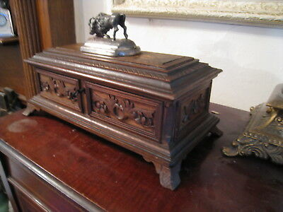 Old carved wooden casket box with metal beast on lid