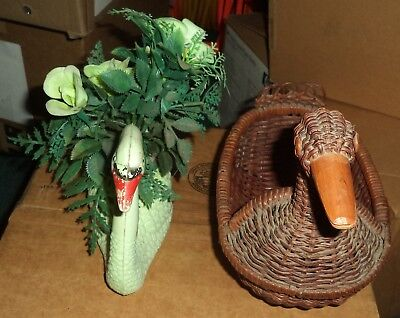 two swan centerpiece one is green plastic and the other one is brown wicker