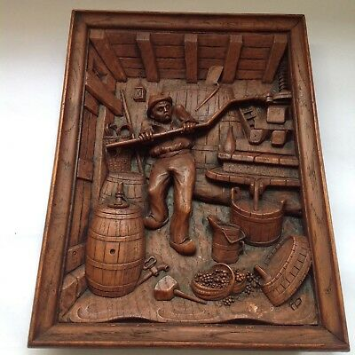 A vintage Black Forest style cast resin & wood plaque, image of man making wine
