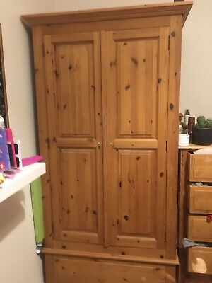 Large solid pine wardrobe with wooden finish. Large drawer at base.