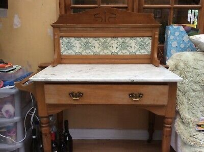 Antique pine washstand with white marble top and green and white tiled back