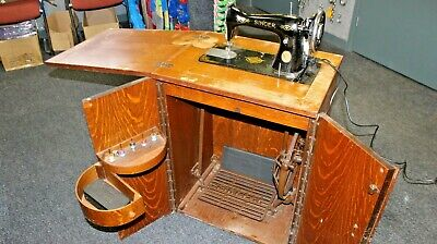 Vintage Singer treadle sewing machine with accessories in cabinet. 1940