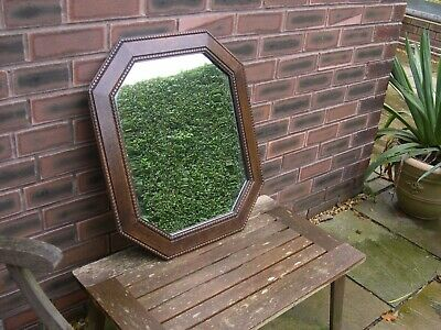 An old octagonal shaped mirror with attractive wooden frame.